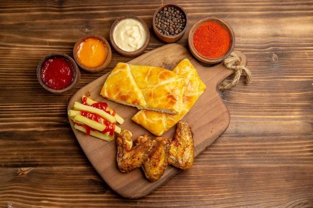 Vista de cima de longe frango e tigelas de torta com temperos e molhos coloridos ao lado de dois pedaços de asas de frango para torta e batatas fritas com ketchup na tábua de corte