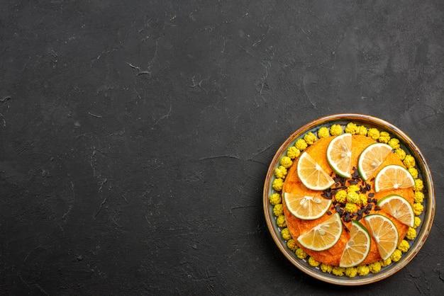 Vista de cima de longe frutas cítricas e bolo apetitoso de chocolate com chocolate e frutas cítricas no lado direito da mesa preta