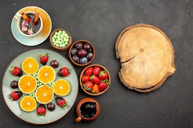 Vista de cima de longe frutas uma xícara de chá uma xícara de chá com cobertura de chocolate, morango picado de laranja e balas verdes e tigelas de frutas vermelhas e doces ao lado da tábua