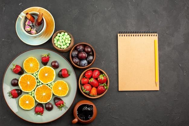 Vista de cima de longe frutas uma xícara de chá uma xícara de chá com cobertura de chocolate, morango picado, laranja, balas verdes e tigelas de frutas vermelhas e doces ao lado do caderno e lápis
