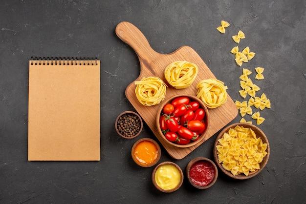 Vista de cima de longe macarrão no tabuleiro tigelas de tomate e macarrão na tábua de corte ao lado do caderno de creme e diferentes molhos, especiarias, macarrão na mesa