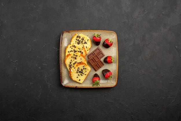 Vista de cima de longe, pedaços de bolo deliciosos morangos cobertos de chocolate e pedaços de bolo com chocolate em um prato quadrado na mesa escura