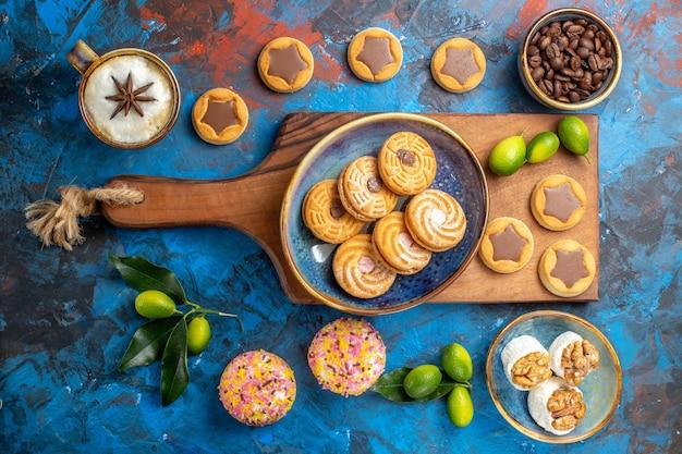 Vista de cima de longe placa de madeira de doces com biscoitos ao lado dos diferentes grãos de café de doces
