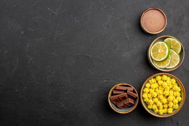 Vista de cima de longe tigelas de limão e balas de diferentes doces fatias de chocolate de limão e creme de chocolate no lado direito da mesa