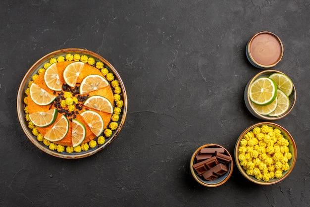 Vista de cima de longe tigelas de limas e doces de diferentes doces fatias de chocolate de limão e creme de chocolate e bolo com frutas cítricas apetitosas