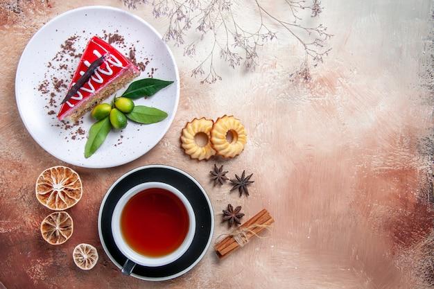 Vista de cima de longe um bolo, biscoitos, canela, palitos, uma xícara de chá, prato, bolo