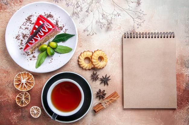 Vista de cima de longe um bolo, biscoitos, canela, uma xícara de chá, prato, bolo, creme, caderno