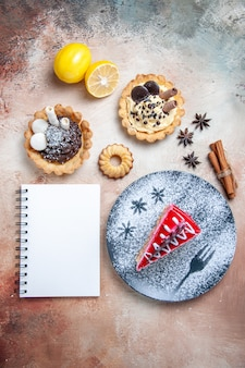 Vista de cima de longe um bolo um bolo canela limão, anis estrelado, biscoitos, caderno, bolinhos