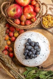 Vista de cima de longe um bolo um bolo com uvas pretas cesta de maçãs bagas passas espigas