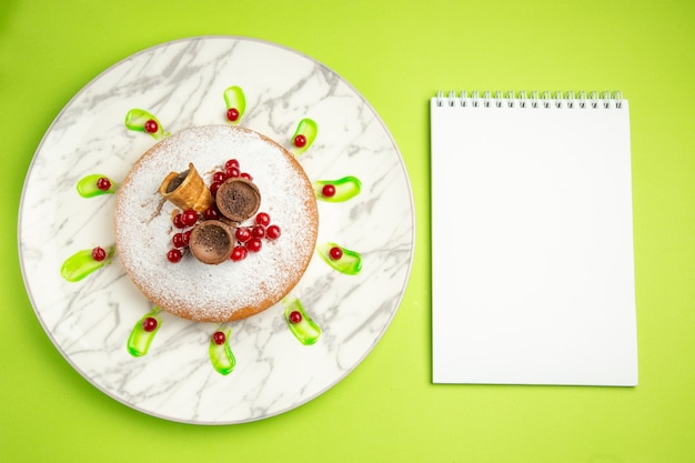 Vista de cima de longe um bolo um bolo com waffles, bagas, caderno branco