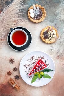 Vista de cima de longe um bolo uma xícara de chá um bolo frutas cítricas cupcakes canela anis estrelado