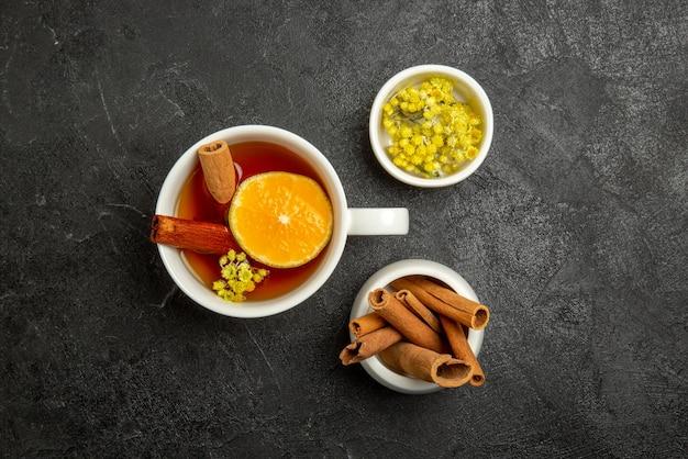 Vista de cima de longe uma xícara de chá com limão uma xícara de chá com limão e tigelas de frutas vermelhas e paus de cinnabon no centro da mesa