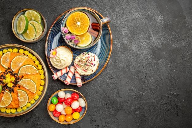 Vista de cima de longe uma xícara de chá de ervas com frutas cítricas e doces e cupcakes com creme e uma xícara de chá de ervas no pires azul sobre a mesa