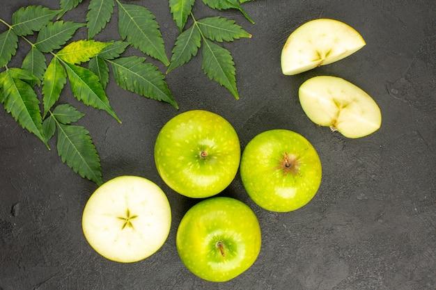 Vista de cima de maçãs verdes frescas inteiras e picadas e hortelã em fundo preto
