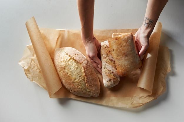 Vista de cima de mãos humanas colocando pão fresco em papel manteiga