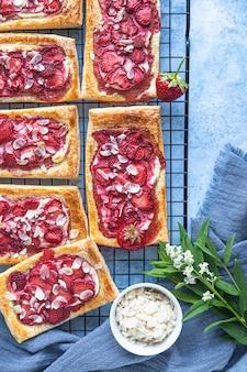 Vista de cima de mini tortas de massa folhada com cream cheese e morango decorada com amêndoa. fundo de concreto azul.