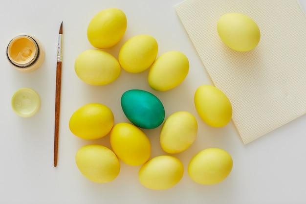 Vista de cima de ovos de páscoa em amarelo pastel com detalhes verdes e pincel com composição mínima em fundo branco, copie o espaço