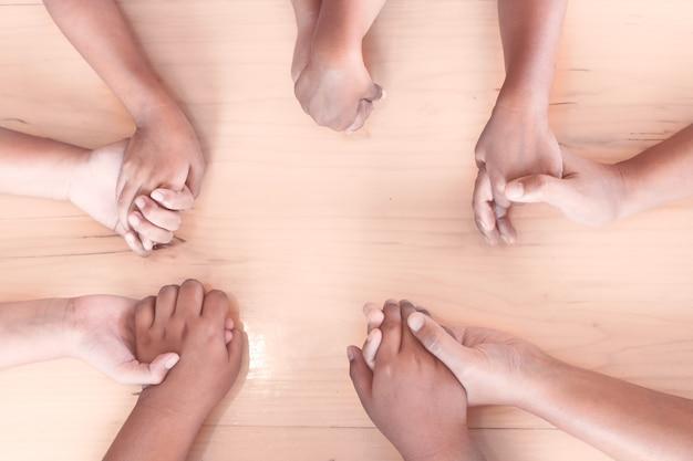 Vista de cima de pais e filhos de mãos dadas e rezando juntos na mesa de madeira