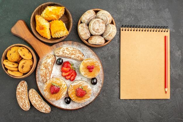 Vista de cima de panquecas deliciosas com frutas e bolos doces no chão escuro