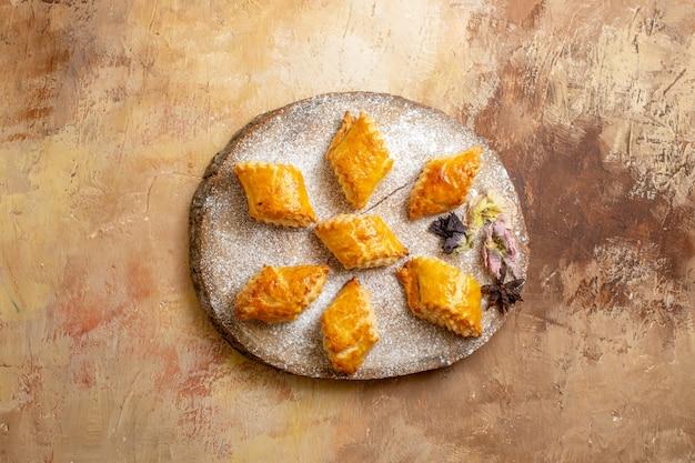 Vista de cima de pastéis doces para chá no chão claro