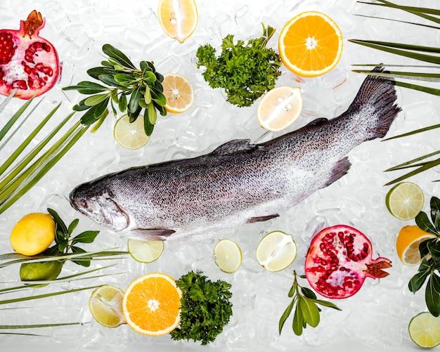 Vista de cima de peixe cru no gelo, rodeado de frutas