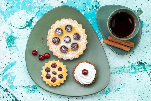 Vista de cima de pequenos bolos deliciosos e assados junto com chá de canela com frutas em azul claro, bolo de chá doce assar torta de frutas