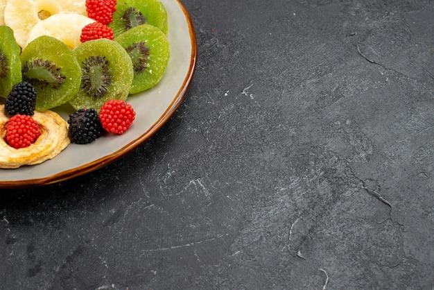 Vista de cima de perto anéis de abacaxi secos com kiwis secos e maçãs na parede cinza-escura fruta seca doce de açúcar