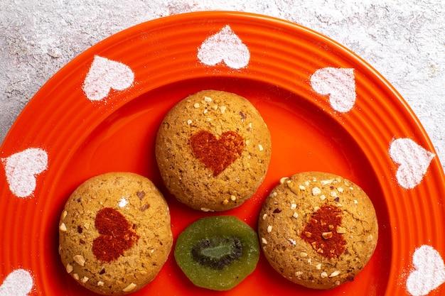 Vista de cima de perto biscoitos de açúcar dentro do prato em um bolo doce de biscoito de superfície branca