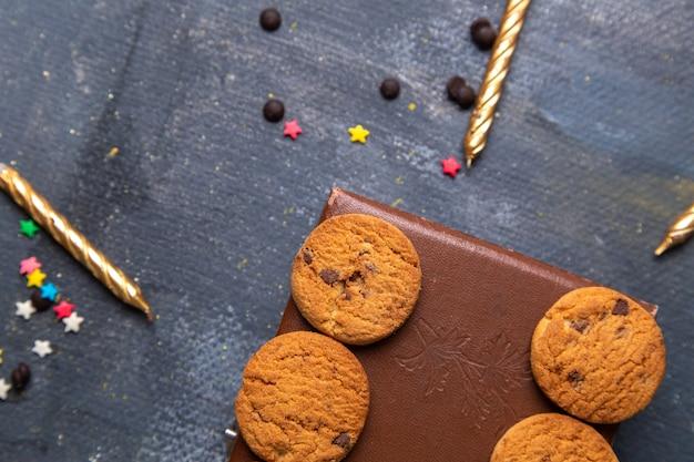 Vista de cima de perto biscoitos de chocolate saborosos na caixa marrom com velas no fundo cinza escuro.