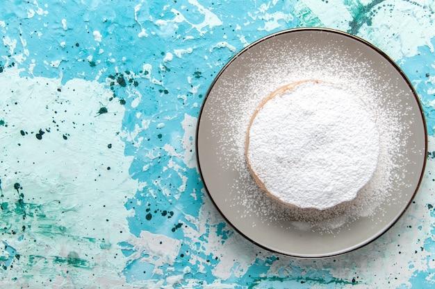 Vista de cima de perto bolo redondo com açúcar em pó dentro do prato na superfície azul claro bolo assar biscoito açúcar doce cor de chá