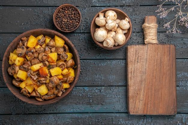 Vista de cima de perto comida em uma tigela de prato de batatas e cogumelos ao lado de uma tigela de pimenta preta, tigela de tábua de corte de cogumelos brancos e ramos