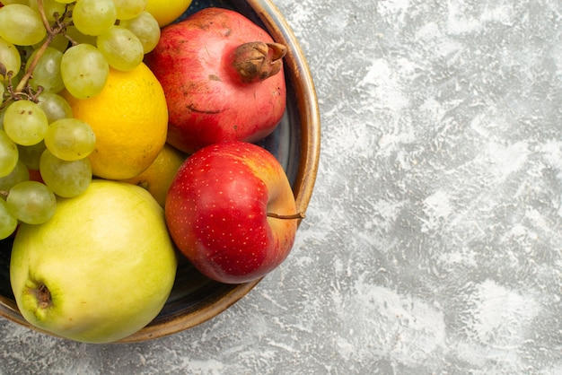 Vista de cima de perto composição de frutas frescas maçãs uvas e outras frutas no fundo branco frutas maduras frescas vitamina de cor madura