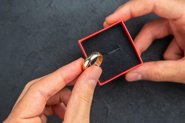 Vista de cima de perto conceito de proposta de casamento homem com as mãos segurando um anel de casamento