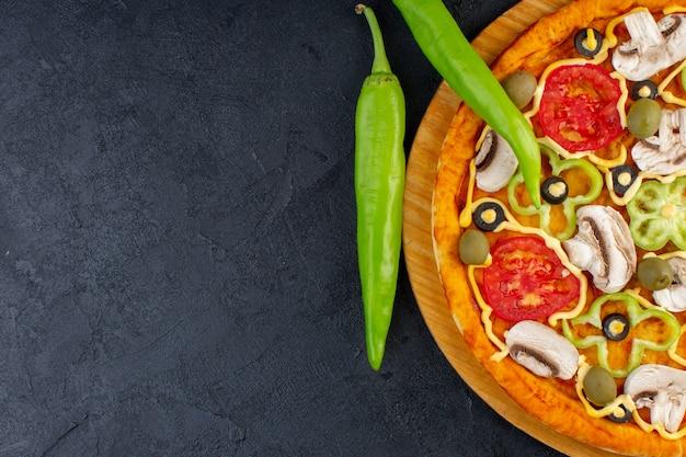 Vista de cima de perto deliciosa pizza de cogumelos com tomates vermelhos, pimentões, azeitonas e cogumelos, tudo fatiado por dentro no fundo escuro.