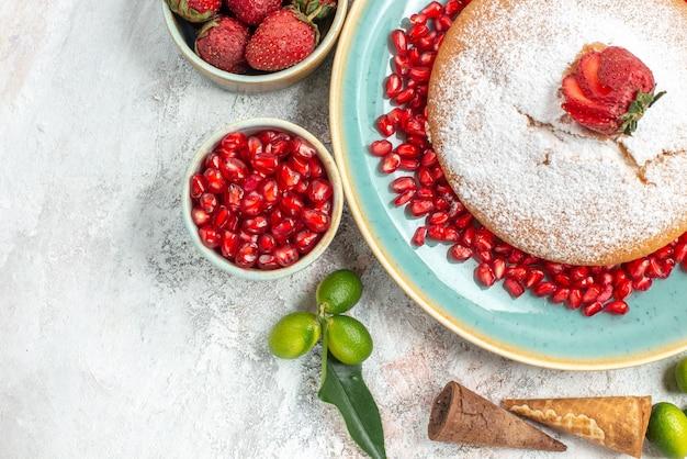 Vista de cima de perto doces um bolo com frutas cítricas de romã taças de morangos romã