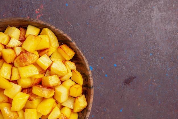 Vista de cima de perto em fatias de batatas dentro de um prato marrom no espaço escuro