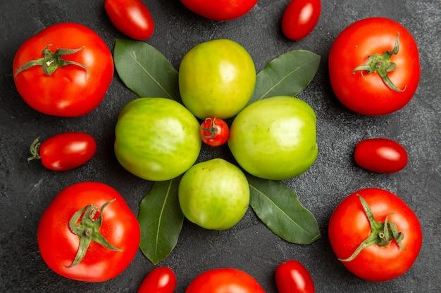 Vista de cima de perto folhas de louro de tomates vermelhos e verdes ao redor de um tomate cereja em solo escuro