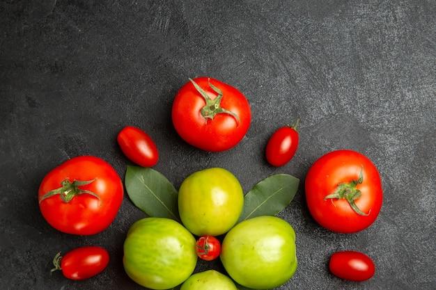 Vista de cima de perto folhas de louro em tomates vermelhos e verdes ao redor de um tomate cereja no fundo de um solo escuro com espaço de cópia