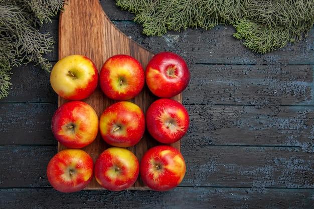 Vista de cima de perto maçãs a bordo de nove maçãs amarelo-avermelhadas em uma tábua de corte marrom em uma mesa cinza e galhos de árvores
