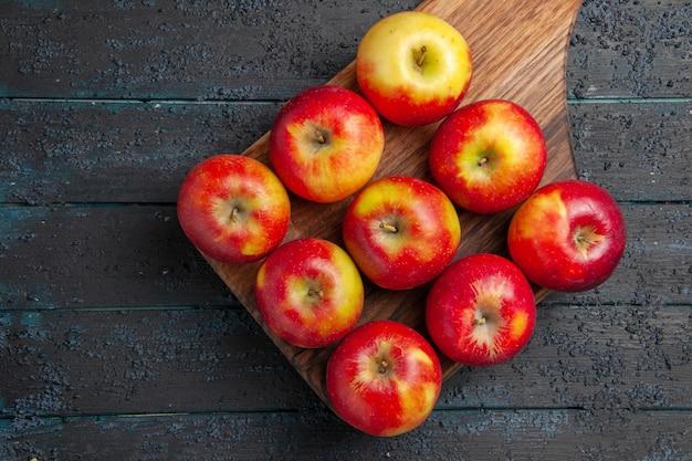Vista de cima de perto maçãs a bordo de nove maçãs amarelo-vermelhas em uma tábua de madeira na mesa cinza