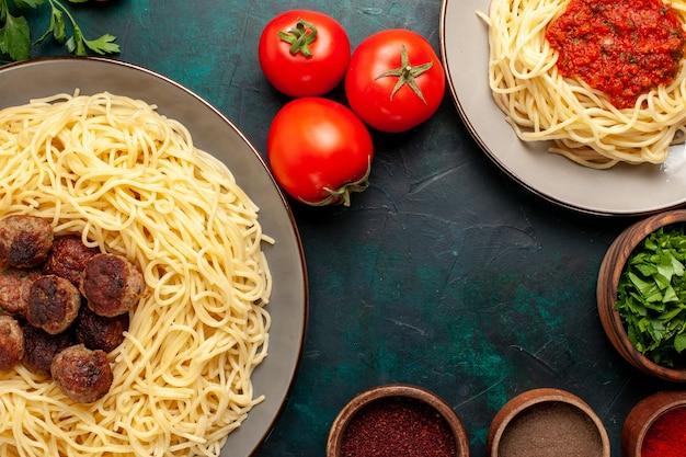 Vista de cima de perto massa italiana cozida com carne e temperos na superfície azul escura