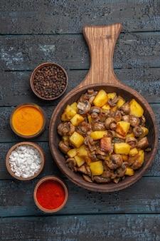 Vista de cima de perto o prato de comida e temperos um prato de cogumelos e batatas na tábua e diferentes temperos ao redor