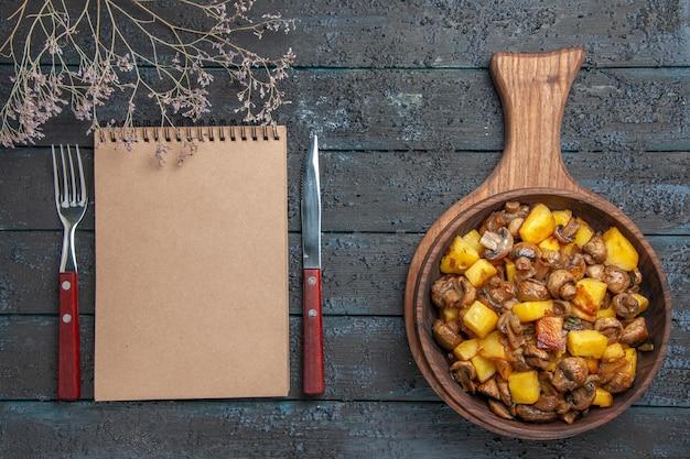 Vista de cima de perto o prato e o caderno, um prato de batatas e cogumelos na tábua e um caderno entre o garfo e a faca