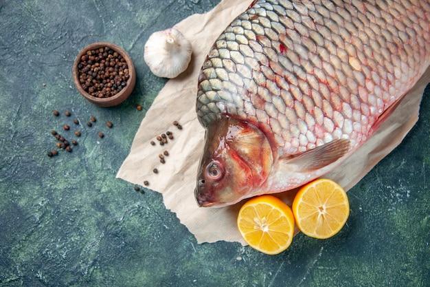 Vista de cima de perto peixe cru fresco com pimenta e limão em fundo azul escuro