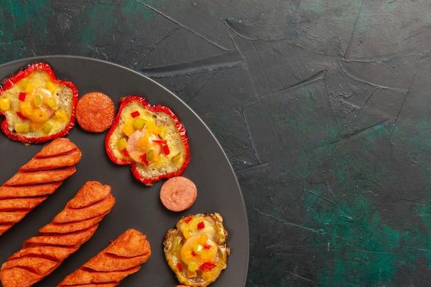 Vista de cima de perto pimentões cozidos com linguiças fritas dentro do prato na superfície verde-escura
