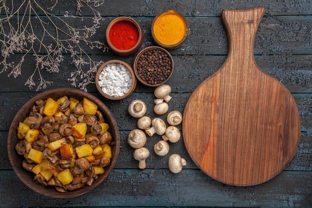Vista de cima de perto placa de prato e prato de especiarias de cogumelos e batatas ao lado de ramos de especiarias coloridas de cogumelos brancos e uma tábua de cortar