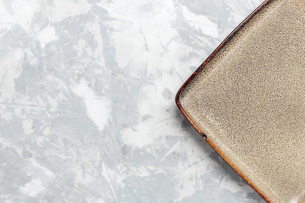 Vista de cima de perto prato quadrado vazio de cor marrom na superfície branca prato de cozinha comida cutelaria