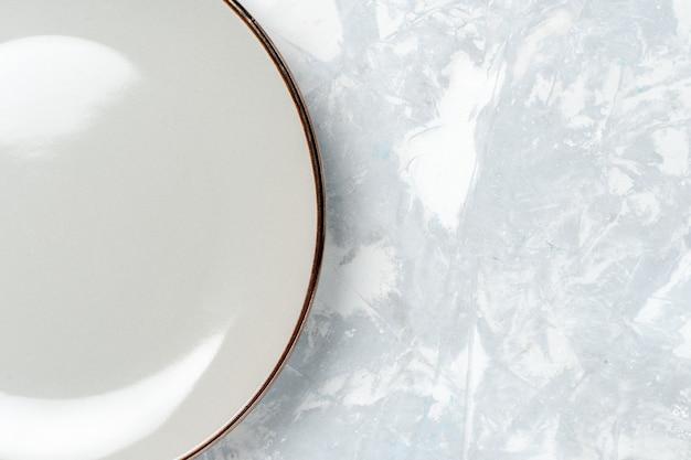 Vista de cima de perto prato redondo vazio na parede branca prato cozinha comida foto cutelaria cor