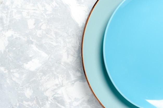 Vista de cima de perto pratos redondos vazios de cor azul na parede branca prato de cozinha comida talheres cor de vidro