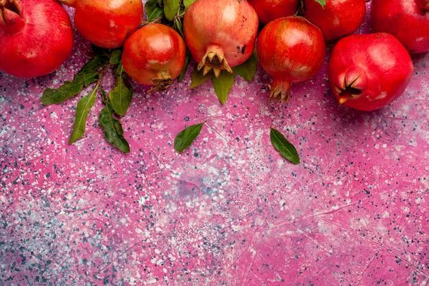 Vista de cima de perto romãs vermelhas frescas com folhas verdes na parede rosa frutas cor de suco fresco